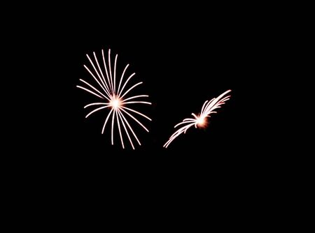 Two white fireworks expolde during a fireworks display close to each other. Reklamní fotografie