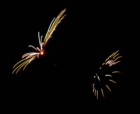 Fireworks explode in the black sky leaving room for copy print between them.