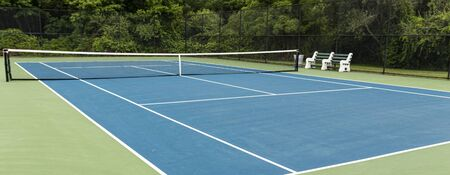 A blue tennis court inside a black fence with be3nches in the middle surrounded by tall trees in the background.