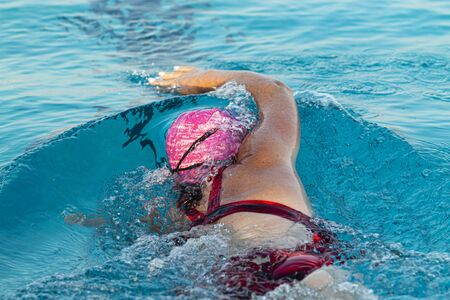 A female swimmer pushing off of the wall while training in an outdoor pool wearing a pink swim cap. Reklamní fotografie
