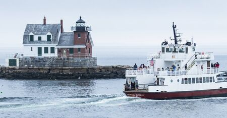 Rockland, Maine, USA - 5 August 2017: Rockland Breakwater Lighthouse in Rockland Maine with the North Haven Ferry ship passing it heading out to sea.