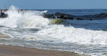An active atlantic icean waves are crashing along the shore and a jetty off of the coast of Fire Island New Yorks Ocean Beach.
