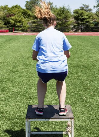 A female athlete is jumping onto a plyo box which is on a green turf field during cross training strength and agility practice at summer camp for runners.