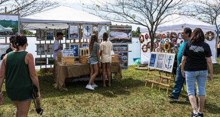 Babylon, New York, USA - 8 September 2019: People enjoying a sunny day walking and shopping for art and crafts around Argyle Lake during the annual Babylon Beautification Society Fair.