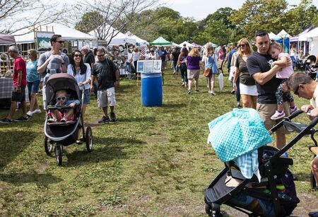 Babylon, New York, USA - 8 September 2019: Families enjoying a sunny day walking and pushing strollers around Argyle Lake during the annual Babylon Beautification Society Fair.