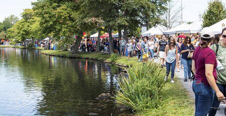 Babylon, New York, USA - 8 September 2019: People enjoying a sunny day walking around Argyle Lake during the annual Babylon Beautification Society Fair. Editöryel