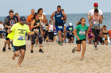Babylon, New York, USA - 24 June 2019: Hundreds of runners are running a race on the beach as part of the New York State Parks Summer Series of races. Editöryel