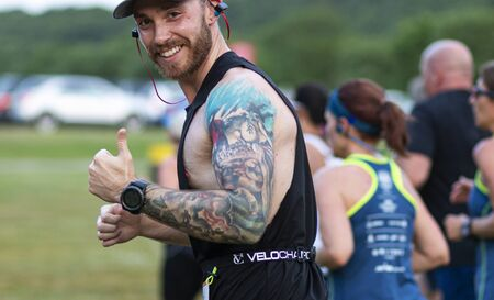 Kings Park, New York, USA - 17 June 2019: runner with tottooed arm giving thumbs up smiling at the camera during the summer series 10K at Sunken Meadow State Park.