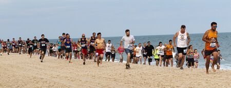 Babylon, New York, USA - 24 June 2019: Hundreds of runners are running a one mile race on the beach as part of the New York State Parks Summer Series of races.