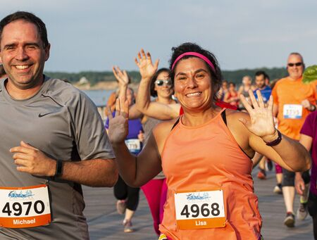 Kings Park, New York, USA - 17 June 2019: runners on the boardwalk smiling and waving at the camera during the summer series 10K at Sunken Meadow State Park.