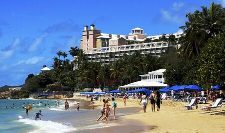 St. Thomas , Virgin Islands - 18, February 2015: Tourists enjoying a beautiful day on a beach in St. Thomas Virgin Islands with hotel on hill above.