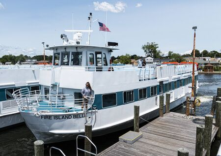 Bay Shore, New York, USA - 22 June 2019: A worker on the Fire Island Bell Ferry ship is about to throw a rope on a piling as the ship returns to the main land with passangers.