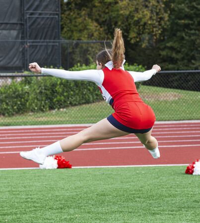 A high school teenage cheerleader in a red and white uniform is jumping in the air practicing her routine before her performance.