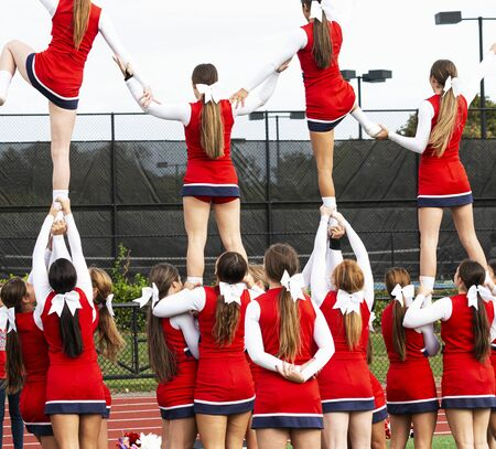 High school teenage cheerleaders holding four teammates in the air and each of them holding one another practicing for a routine. Stok Fotoğraf