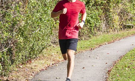 A high school boy is running toward the camera on a tar path surrounded by green bushes while training for cross country running.