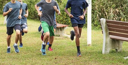 High school boys are running together on the grass in a park passing benches during cross country training. Stok Fotoğraf