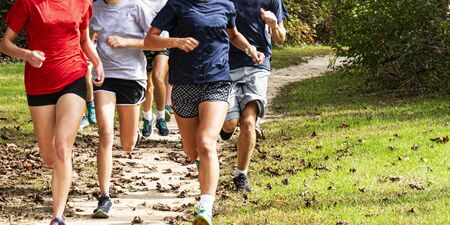 A group of high school cross country runners are running fast training on a dirt path covered in leaves in the woods.