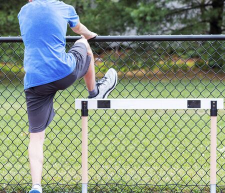 Rear view of a high school track and field athlete is performing a hurdle drill using a fence to balance at practice. Stok Fotoğraf