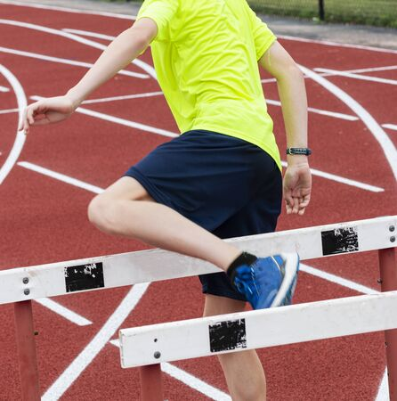A runner in a neon green shirt is doing a hurdle walk over drill on a red track in the summer. Stok Fotoğraf