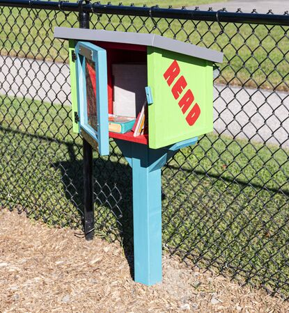 A wooden box on a post in a public park designed for people to take and leave free books with the door open showing books inside. Stok Fotoğraf