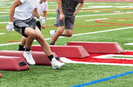 Three football players are running between red barriers on a turf field during summer camp training. Stok Fotoğraf