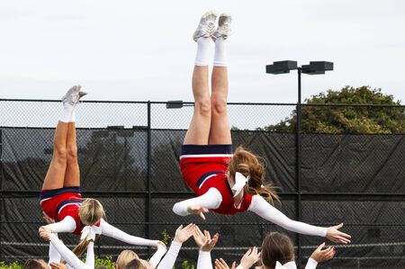 Two high school teenage cheerleaders in red and white uniforms are being flipped in the air with their teammates ready to catch them while practicing their routine.