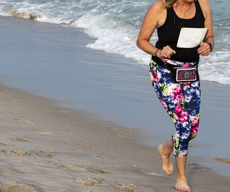A women runs on the beach during a race with bare feet and very colorful spandex on the sand next to the ocean carrying her phone around her waist. Stok Fotoğraf