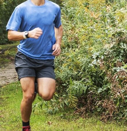 A runner is on a dirt path with grass in a park turning around very tall bushes. Stok Fotoğraf