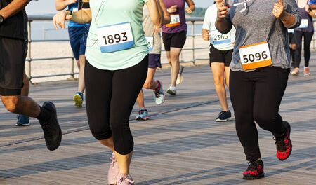 Many runners on a boardwalk next to the beach are racing a 10K on a suny summer night at Sunken Meadow State Park in New York.