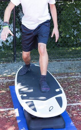 A young runner is cross training standing on a portable surfboad machine for stability and strength training in the shade on a track at summer camp.