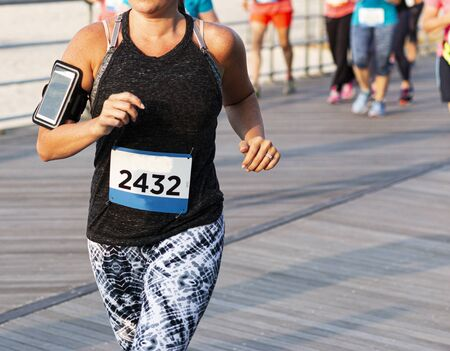 A female runner is running a 10K race on a boardwalk with a phone strapped on her arm and the runners behind her blurred.