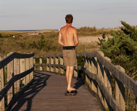 Rear view of a male riding a skateboard barefoot with no shirt on the boardwalk leading to the Fire Island Lighthouse in the summer. Stock Photo