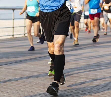 Die Läuferlandung heilt bis zu den Zehen, während sie einen 10 km-Rennen und schwarze Kompressionsstrümpfe auf einer Promenade am Strand trägt.