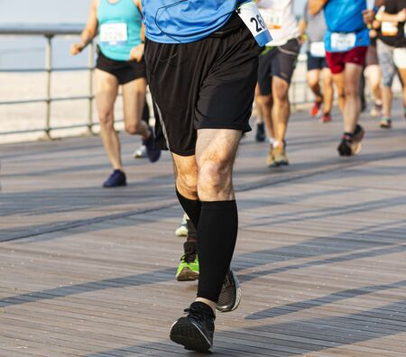 Runner landing heal to toe while racing a 10K and wearing black compression socks on a boardwalk by the beach.