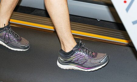 A persons feet are running and walking on a treadmill inside. Banco de Imagens