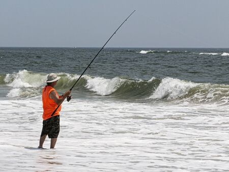 A man in an orange shirt is surfcast fishing into the ocean with small waves breaking in front of him.