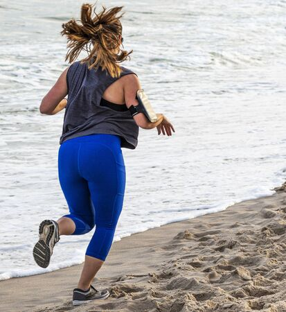 Rear view of a waomen in blue spandex running next to the water on sand with a cell phone strapped to her arm to listen to music.