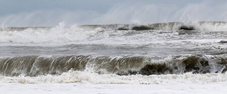 The Atlantic Ocean off of the coast of Fire Island New York during a tropical storm with strong winds blowing the water backwards.