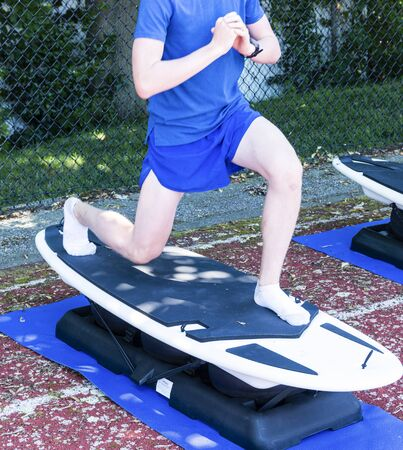 A teenage runner performing lunges on a unstable surboard machine for strength and stability practice during a summer camp in the shade on a track.