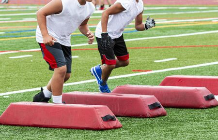Two high school feetball players synchronized while training running between red barriers at summer camp practice on a green turf field.