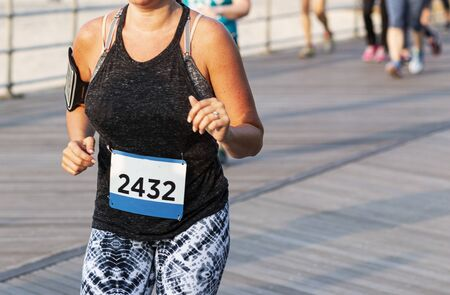 A women is running a 10K race on a boardwalk while wearing a cell phone strapped to her right arm. Reklamní fotografie