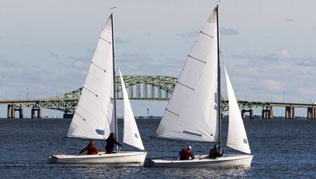 Close up of two two person saiboats sailing on a cold December 2019 day in the Great South Bay with the Bridge in the background.