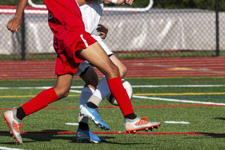 Two male high school soccer players are fighting for possesion of the ball during a game on a green turf field.