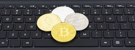 Bitcoin, litecoin, ethereal and ripple coins on top of a black computer kerboard with white letters.