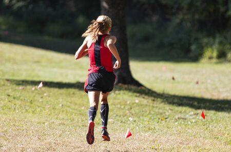Widok z tyłu prowadzącej dziewczęcy wyścig cross country za małymi czerwonymi flagami wyznaczającymi trasę.
