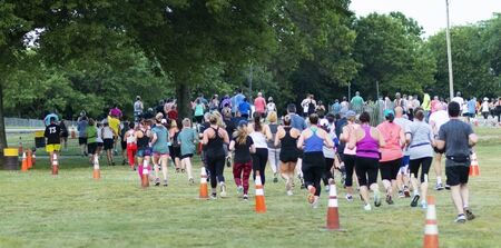 Orange cones mark the 10K cousre with a crowd of runners racing on the grass at Sunken Mewadow State Park.
