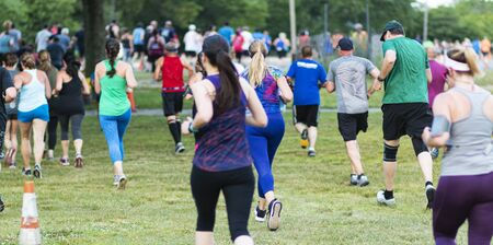 Rear view of male and female runners racing a 10K on a grass field at Sunken Meadow State Park. Stock fotó