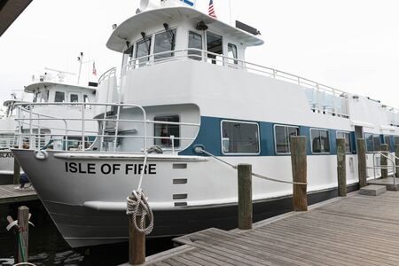 Bay Shore, New York, USA - 6 October 2019: Side view of the Isle Of Fire Fire Island ferry tied up to the docks with other ferries behind it.