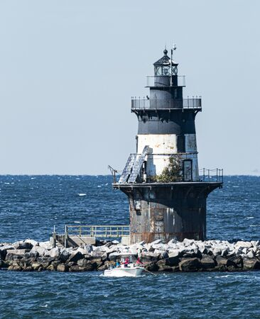 People are in a small boat fishiing infront of the Orient Point Lighthouse on a windy day.