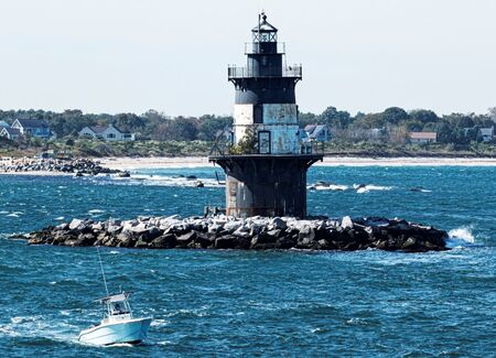 A boat is passing the Orient Point Lighthouse on a windy day with rough seas and the beach in the background.